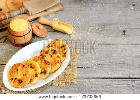 Delicious couscous patties with sausage and herbs. Crispy couscous patties on a plate and on vintage wooden background with copy space for text. Rustic style