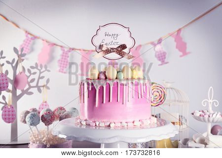 Delicious Easter cake decorated with colorful sweet eggs and greeting card on stand