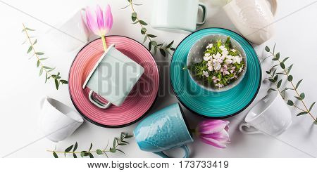 Spring tableware crockery concept with tulips flowers pastel color white background. Textured ceramic plates dishes mugs. Mother woman day gift idea