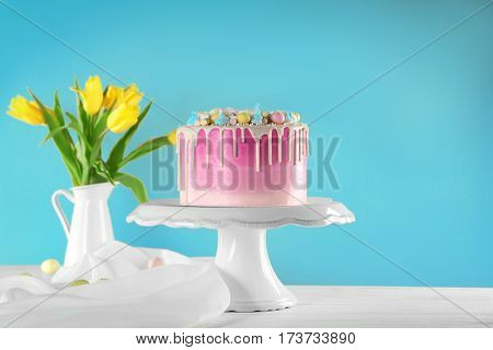 Vintage stand with beautiful Easter cake on color background