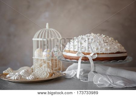 Tasty Easter cake with cookies on light background