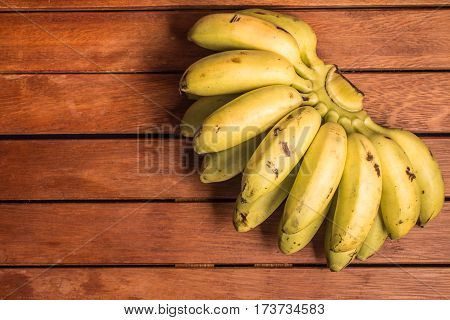 Lady Finger Banana Ouro over a wooden table