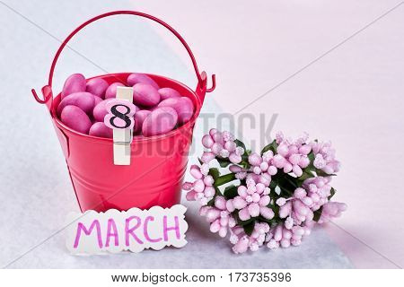 Bucket with sweets and flowers. Celebrate the power of womanhood.