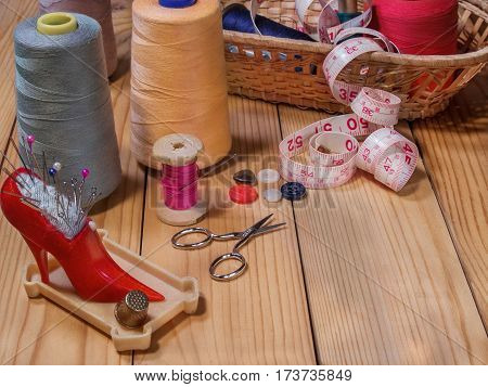 Needle bed with needles and pins thread on a spool thread on large spools scissors thimble tape measure spools of thread in a basket from straw on a wooden background