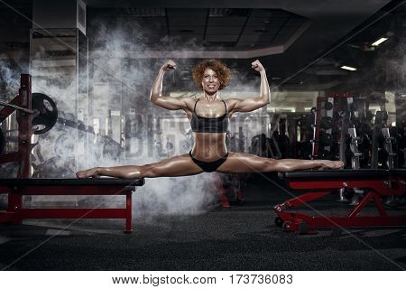 Pretty sporty strong slim and fit young woman sitting doing split and stretching exercises sitting on a full split. In the gym