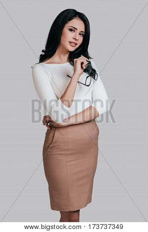 Beautiful business lady. Gorgeous young woman in smart casual wear keeping arms crossed and looking at camera while standing against grey background