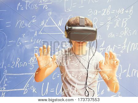 Teenager wearing VR virtual realty glasses and learning math - virtual learning concept