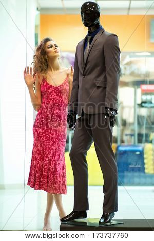 Pretty girl or beautiful woman with long curly hair wearing pink polka dot dress looks at fashionable male mannequin in suit in shop window