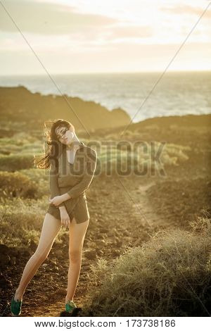 Pretty Girl Wearing Brown Shirt And Green Gumshoes On Beach