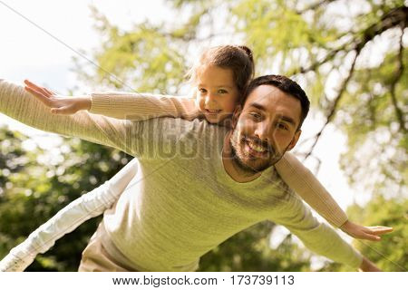 family, parenthood, fatherhood and people concept - happy man and little girl in having fun in summer park