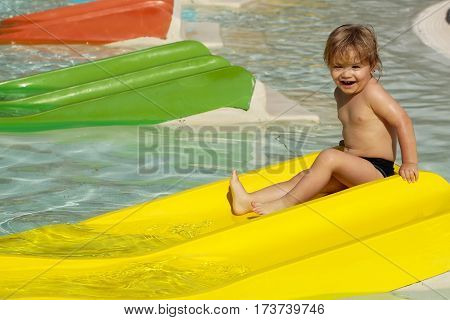 Happy Cute Baby Boy Sliding From Yellow Waterslide