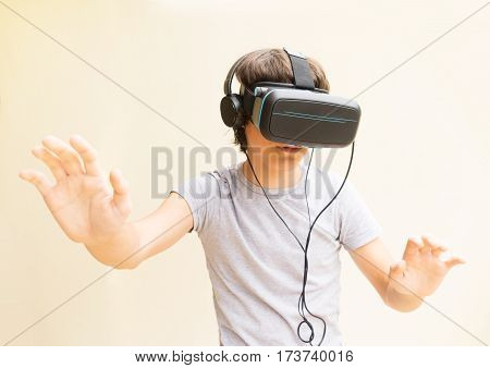 Teenager boy wearing and touching something in VR virtual realty glasses