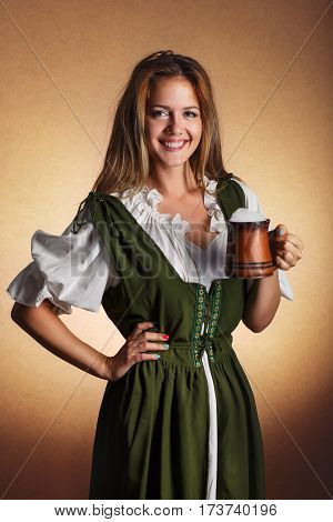 very beautiful woman in tiroler oktoberfest dress with big mug of beer in her hands