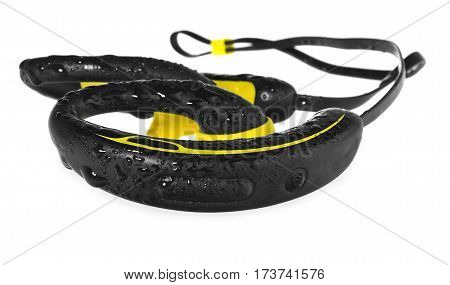 Waterproof headphones earphones yellow and black beaded with water on a blue towel. Headphones for running in the rain isolated on white background with light shadow and reflection.