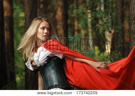 Portrait of a blonde lady in old-fashioned dress and red cloak in a fairy forest