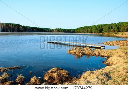 Landscape with a secluded lake, old pier, hay and pine forest around.
