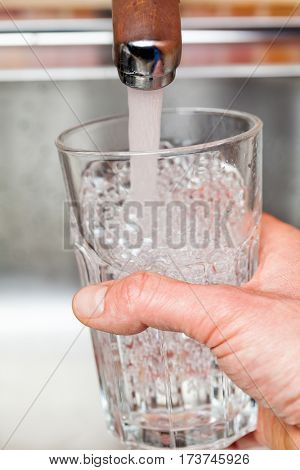 Closeup shot of a man pouring a glass of fresh water from a kitchen faucet