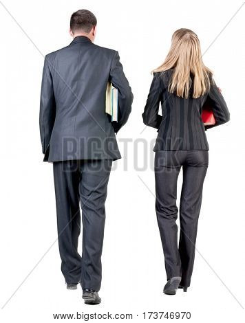 Back view of walking business team. Going young couple (man and woman) with books. beautiful friendly girl and guy in suit together. Rear view people collection. backside view of person.