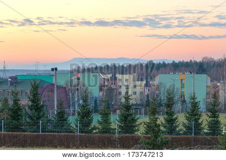City ​​morning landscape. City blocks with mountains in the background.