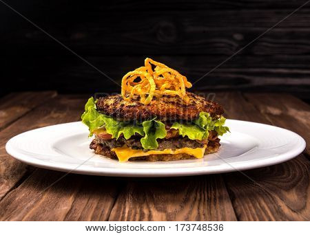 Delicious hamburger potato pancakes bun. latke burger with lettuce, cheese, tomatoes on wooden black background and white plate.