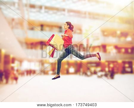 sale, motion and people concept - smiling young woman with shopping bags jumping in air over mall background