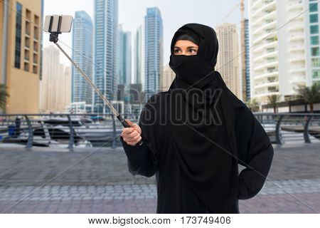 technology and people concept - muslim woman in hijab taking picture with smartphone selfie stick over dubai city street background