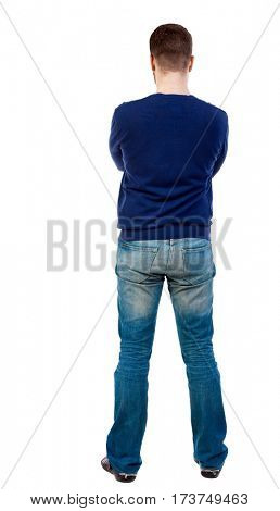 Back view of man in jeans. Standing young guy. Rear view people collection.  backside view of person.  Isolated over white background. Man in jeans and a blue sweater standing with his arms crossed