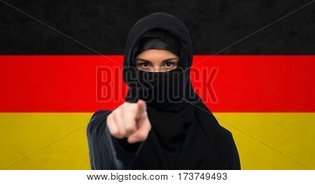 immigration and people concept - muslim woman in hijab pointing finger to you over german flag background