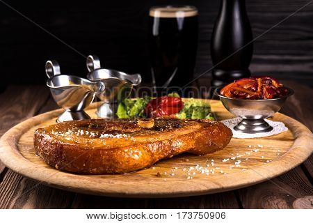 Roasted slice of pork leg with bone. Two sauces, Red beans, onion, bell pepper on wooden background and black glass of beer. Food cocept