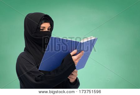 religion, education and people concept - muslim woman in hijab reading book over green chalkboard background
