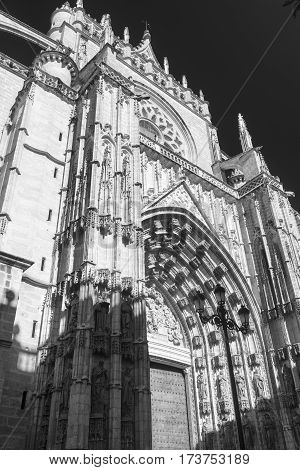 Sevilla (Andalucia Spain): a facade of the cathedral with statues. Black and white