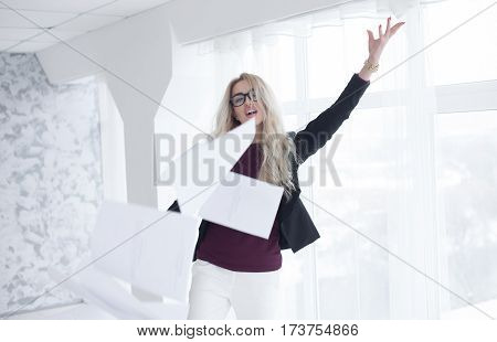 Young businesswoman throws paper document pages in office.