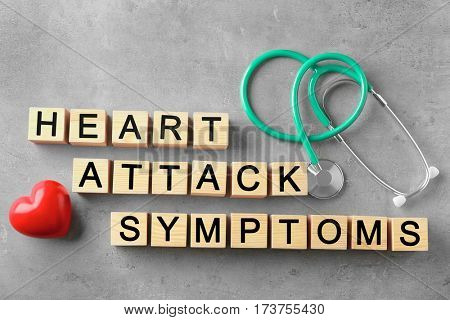 Text HEART ATTACK SYMPTOMS made of wooden cubes and stethoscope on color background