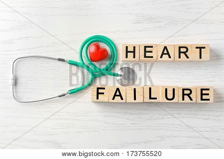 Text HEART FAILURE made of cubes and stethoscope on wooden background
