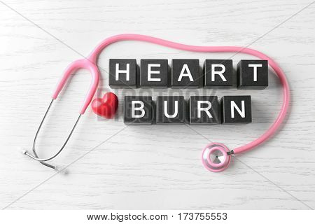 Text HEART BURN made of cubes and stethoscope on wooden background