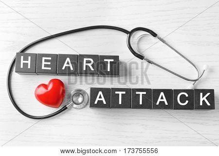Text HEART ATTACK made of cubes and stethoscope on wooden background