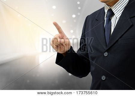 Asian business man finger point up on abstract blurry background