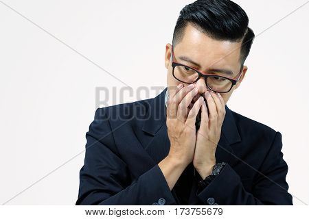 Asian business man with his hands clasped face or seriously depressed