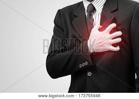 Asian business man with symptoms of heart disease. Chest pain on the left