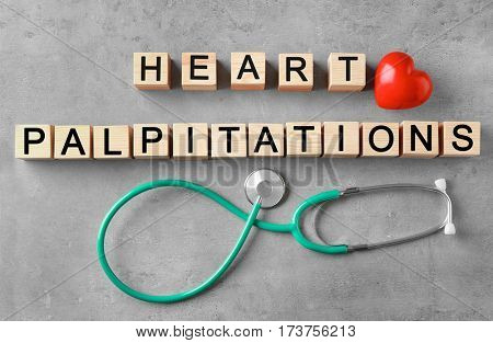 Text HEART PALPITATIONS made of wooden cubes and stethoscope on color background