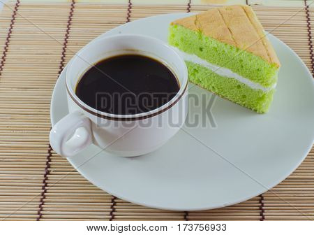 Coffee cup pandan sponge cake isolated on dish White background