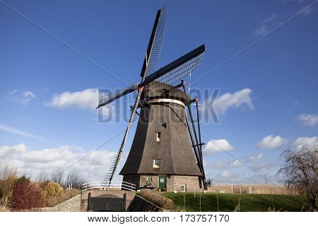The old Dutch windmills, Holland, rural expanses . Windmills, the symbol of Holland. Holland windmill on a canal. Old mill chalk and flour . The beautiful backdrop of the countryside of Holland.