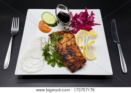 Grilled Norwegian salmon with cucumber, tomato, cabbage and a slice of lemon on the plate with pomegranate sauce