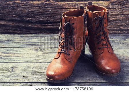Brown women boots on a rustic wooden background