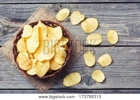 Crispy potato chips on old wooden background . Top view
