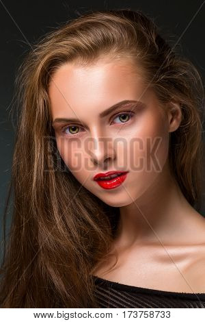 Beauty woman face closeup isolated on black background. Beautiful model girl makeup. Gorgeous lady with long hair and red lips.