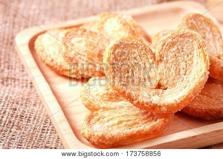 Paddle a butterfly heart shaped patty crispy with sugar in a wooden dish for lovers on Valentine's Day
