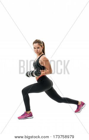 Pretty fitness trainer in black top and leggings exercising with dumbells in studio isolated photo