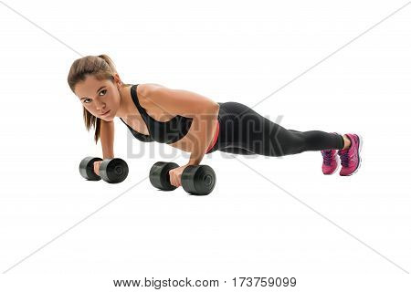 Pretty fitness trainer in black top and leggings doing push-ups on the floor in studio isolated photo