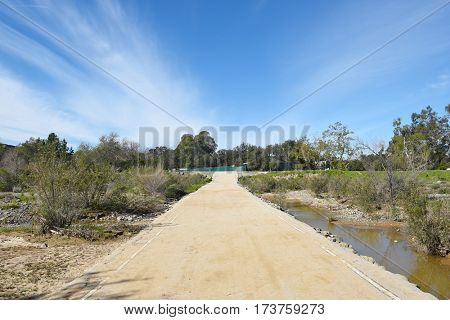 Peters Canyon Road where it crosses Santiago Creek in Irvine Regional Park, Orange County, California. Blue sky with interesting clouds,